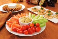 A vegetable platter with crackers topped with lobster pate